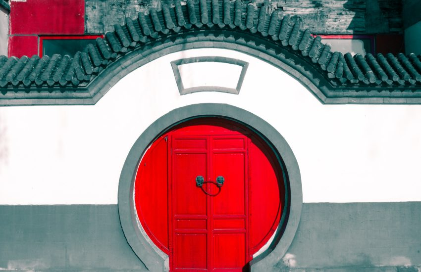 Red circulare Chinese door surrounded by white wall